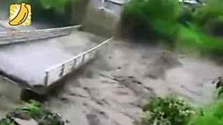 实拍男子围观洪水桥面突断裂 被无情冲走