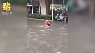 暴雨突袭 一男子坐污水中淡定洗澡