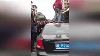 嚣张女子当街爬公交车顶 脱鞋狂砸民警